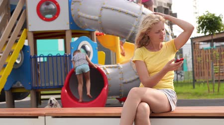 life in a modern city - girl with curly hair in casual clothes sits on a bench near the playground with a smartphone Стоковые видеозаписи