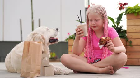 love for pets - beautiful fashion girl with african pigtails eats on the street with her dog