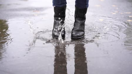 muddy : a girl in black leather boots stumbles in the autumn puddle during the rain in slow motion