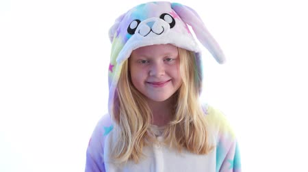 nachtkleding : modern fashion - beautiful blonde girl posing on a white background in kigurumi pajamas, bunny costume - isolated on white Stockvideo
