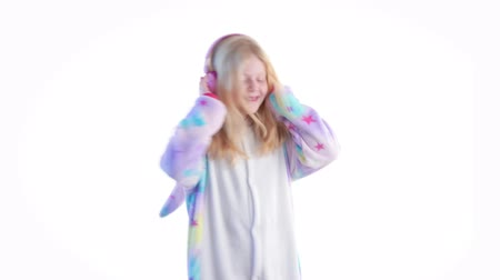 puericultura : modern fashion - beautiful blonde girl listens to music with headphones and dancing on a white background in kigurumi pajamas - isolated on white