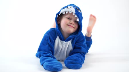 puericultura : cheerful little boy posing on a white background in pajamas kigurumi, blue shark costume Stock Footage