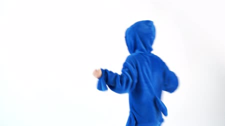 puericultura : cheerful little boy dancing fun on a white background in pajamas kigurumi, blue shark costume Stock Footage