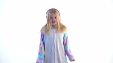 peluş : modern fashion - beautiful blonde girl listens to music with headphones and dancing on a white background in kigurumi pajamas - isolated on white