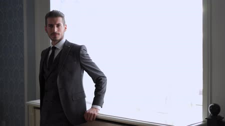 smokin : mens fashion and style. portrait of handsome young groom by the window indoors Stok Video