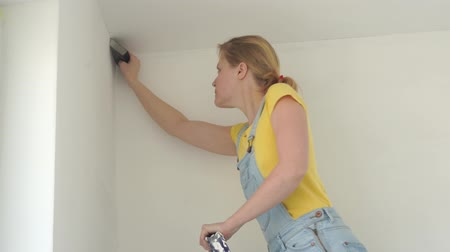 narożnik : repair in the apartment - a young woman of European appearance makes repairs at home