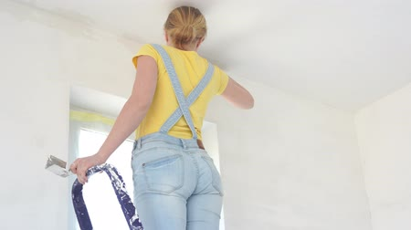 шпатель : repair in the apartment - a young woman of European appearance makes repairs at home