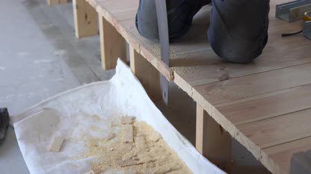 skillful : construction work - a man sawing sawn wooden floor boards Stock Footage