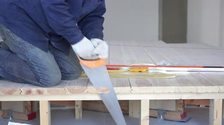 sawn : construction work - a man sawing sawn wooden floor boards Stock Footage