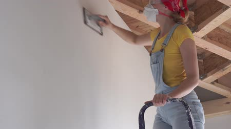 шпатель : repair in the apartment - a young woman of European appearance makes repairs at home - wall surface polishing