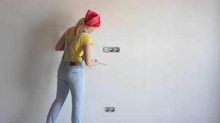 riparazioni : repair in the apartment - a young woman of European appearance makes repairs at home closeup - timelapse