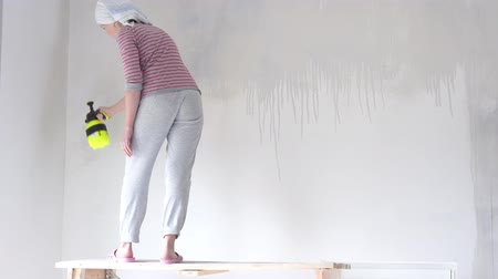 шпатель : repair in the apartment - a young woman of European appearance makes repairs at home - wall priming