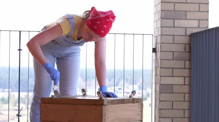 caixa de ferramentas : a woman on a terrace does a non-female job - drills a hole with a screwdriver in a wooden box Stock Footage