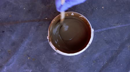 alchemy : painting and repairs - the paint in the bucket is stirred with a stick Stock Footage