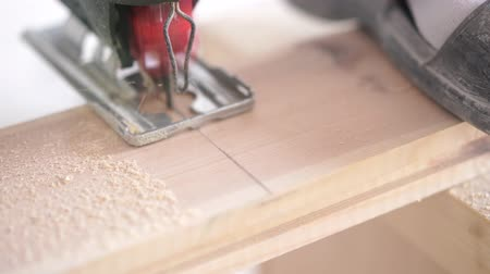 зажимное приспособление : man sawing a wooden board with an electric jigsaw closeup