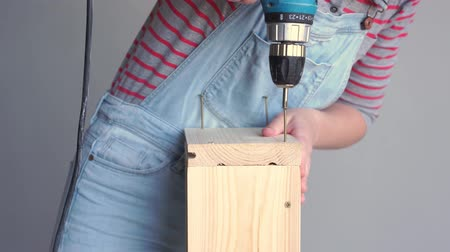 power equipment : a woman does a non-female job - drills a hole with a screwdriver in a wooden box