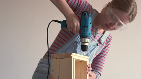 ジグソーパズル : a woman does a non-female job - drills a hole with a screwdriver in a wooden box