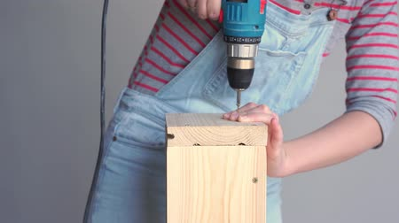 timber cutting : a woman does a non-female job - drills a hole with a screwdriver in a wooden box