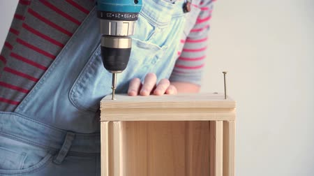 caixa de ferramentas : a woman does a non-female job - drills a hole with a screwdriver in a wooden box, slow motion Vídeos