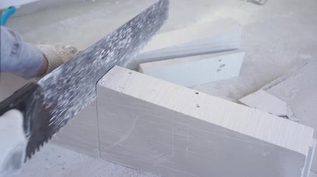 feloszt : beauty slow motion in construction and repair - male builder sawing gypsum tongue-and-groove blocks