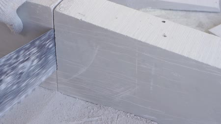 pilka : beauty slow motion in construction and repair - male builder sawing gypsum tongue-and-groove blocks