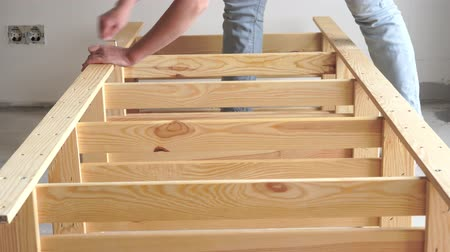 schroef : non-female work. young woman assembles wooden furniture indoors.