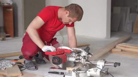 miter saw : woodworking in the house - a young professional male mounts a pine wood floor Stock Footage