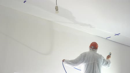 postřikovač : repair of the apartment - professional painter paints the walls with white paint spray gun