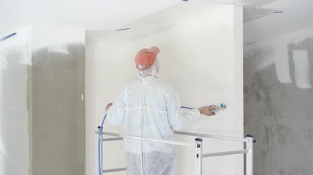 dyeing : repair of the apartment - professional painter paints the walls with white paint spray gun