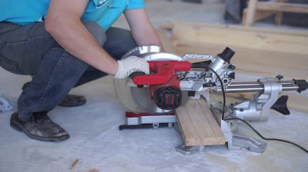miter saw : beauty slow motion. woodworking in the house - a young professional male mounts a pine wood floor Stock Footage