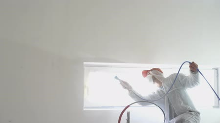 overall : repair of the apartment - professional painter paints the walls with white paint spray gun