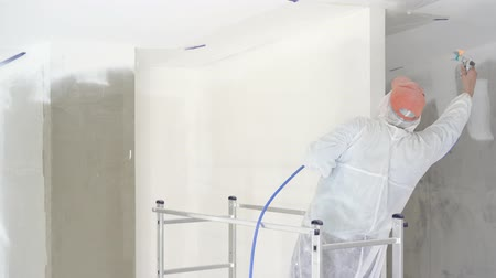 verfrol : repair of the apartment - professional painter paints the walls with white paint spray gun
