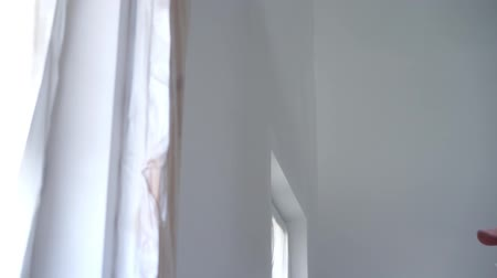 overall : beauty slow motion. repair of the apartment - professional painter paints the walls with white paint spray gun