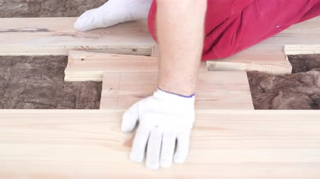 plankenvloer : woodworking in the house - a young professional male mounts a pine wood floor Stockvideo