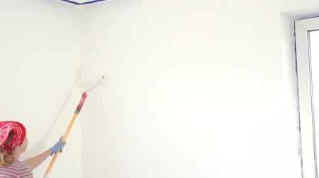 dyeing : beauty slow motion. repair of the apartment - professional painter paints the walls with white paint roller