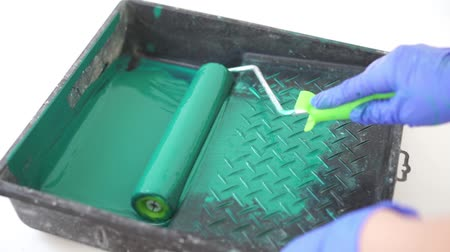 salopette : beauty slow motion. repair of the apartment - rolling green paint roller paint container closeup