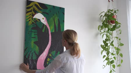 rama obrazu : Moving to a new home. A young blonde woman laying down a picture on canvas in a room.