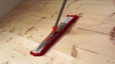 паркет : environmentally friendly coatings. House cleaning. barefoot woman mops wooden floor