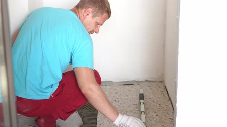 клейкий : Repair and decoration of apartments and houses. Professionals lay porcelain tiles on the floor in the bathroom.