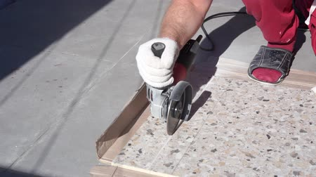 tiled floor : Repair and decoration of apartments and houses. man cuts porcelain tile grinder on the terrace Stock Footage