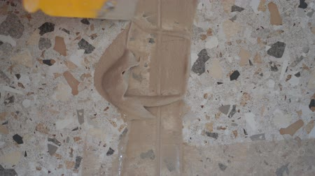 cement floor : Repair and decoration of apartments and houses. woman fugues seams tiles in the bathroom