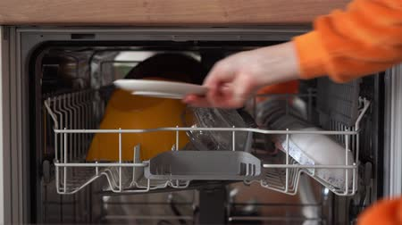 arruela : a woman opens a dishwasher and puts a dirty plate in it