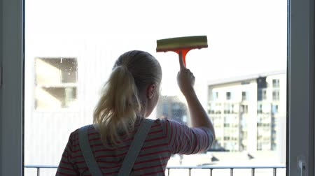 dienstbode : Young woman cleaning the window