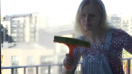 dienstbode : Young woman cleaning the window, slow motion
