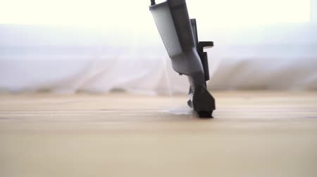 laminát : cleaning a wooden floor with a washing vacuum cleaner, slow motion