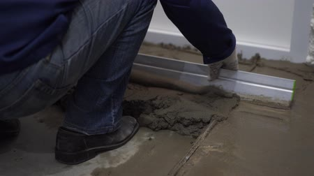 forro : repair of apartments and houses. the builder pours and levels the cement screed on the floor.