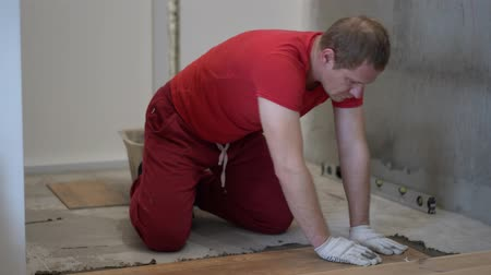 installer : repair and decoration. the tiler puts the porcelain tiles on the floor in the apartment