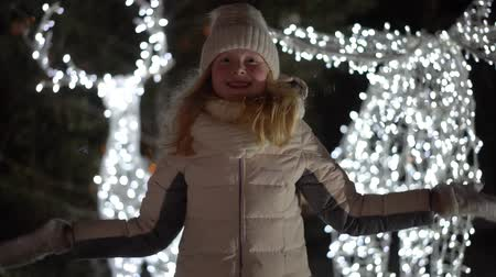 knitted gloves : beautiful slow motion video - a blonde girl throws snow at the camera