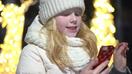 cellen : beautiful blonde girl talking on a smartphone on a Christmas decorated street in winter Stockvideo