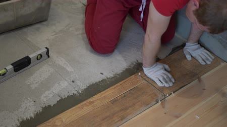 tiled floor : repair and decoration. the tiler puts the porcelain tiles on the floor in the apartment